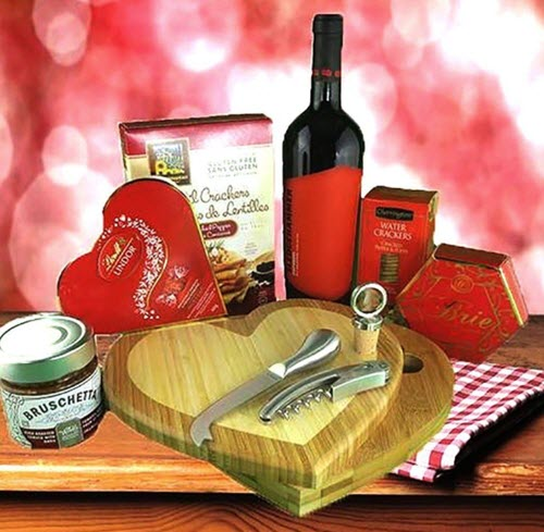 Red background with a heart cutting board, chocolates and wine