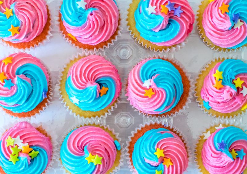 12 cupcakes with pink and blue icing, along with yellow stars