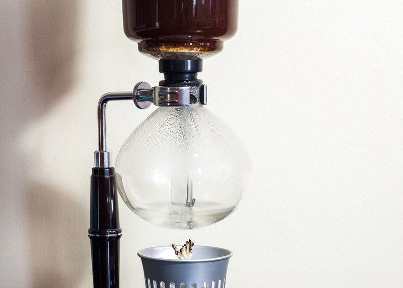 craft coffee being heated by wick and fire on a vacuum coffee pot