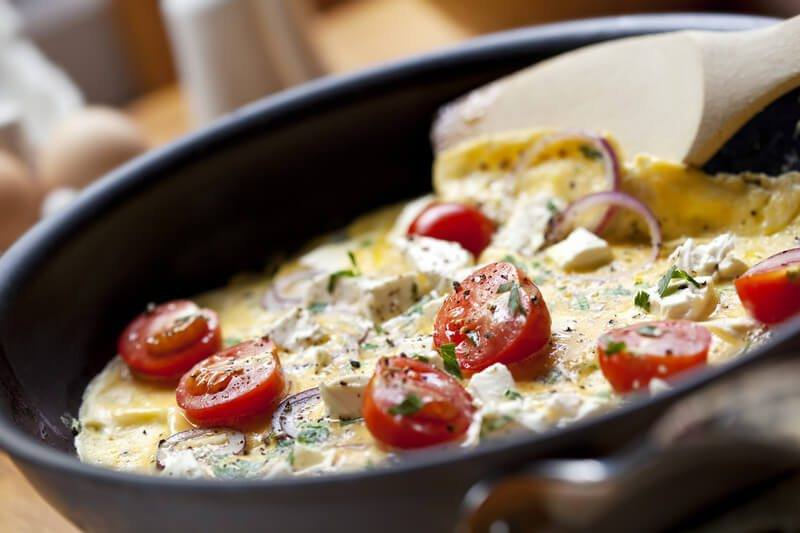Omelet in a pan with tomatoes and cheese