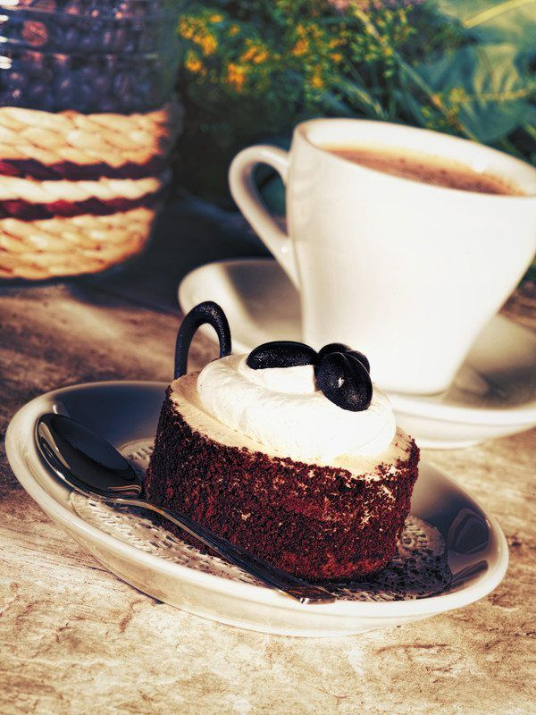cup of coffee with coffee flavored cake and whole bean coffee beans with cream on top.