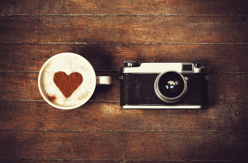 camera with coffee cup and heart design on wooden floor