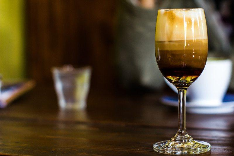multi-layer coffee cocktail in a narrow wine glass