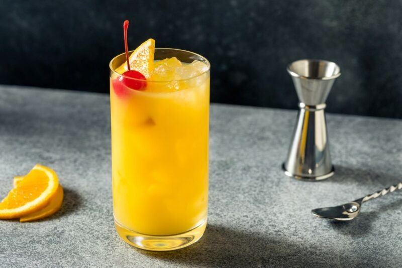 A bench with a Harvey Wallbanger cocktail, a spoon, a jigger, and a wedge of citrus