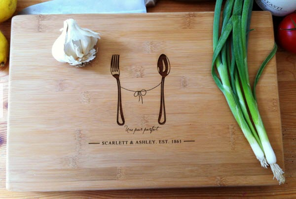 A cutting board with a fork and spoon engraved upon it.