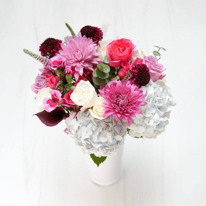 A Signature Collection bouquet from Enjoy Flowers with pink and white blooms in a white vase