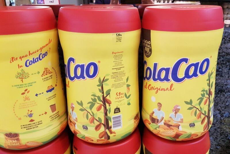 Containers of a chocolate Spanish drink called Cola Cao. The containers are yellow with red lids.