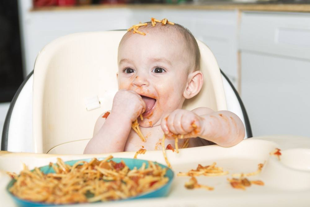 A baby in a high chair eating spaghetti and making a mess