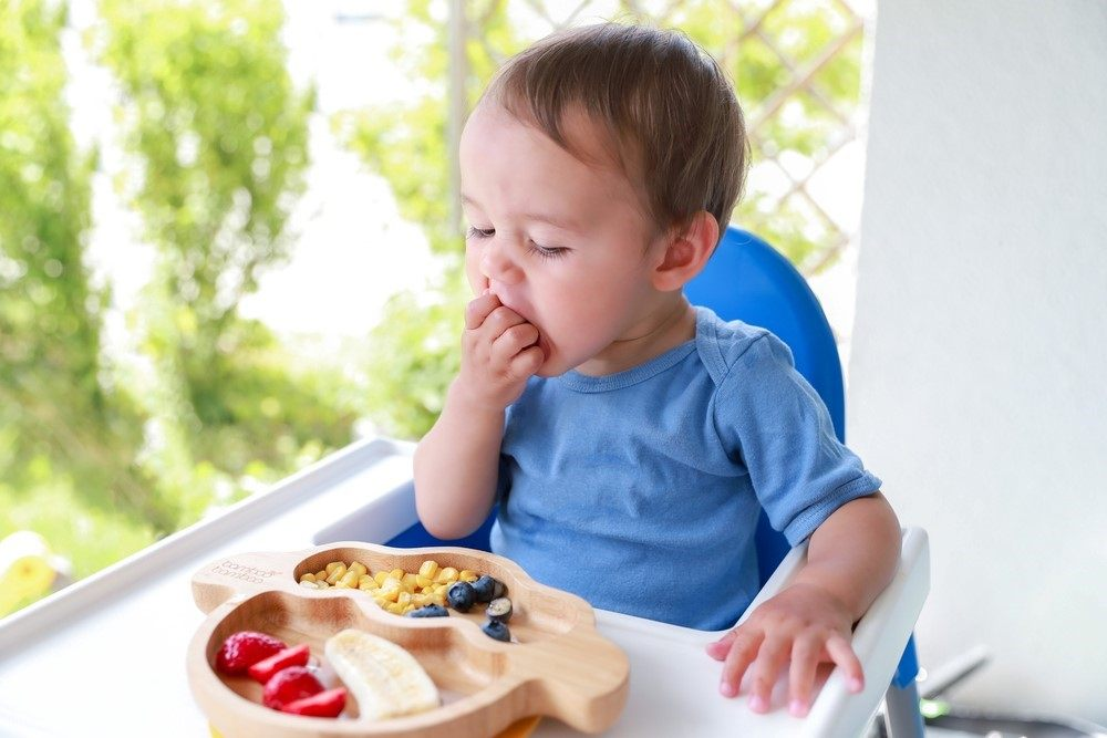 A baby in a high chair eating fruit