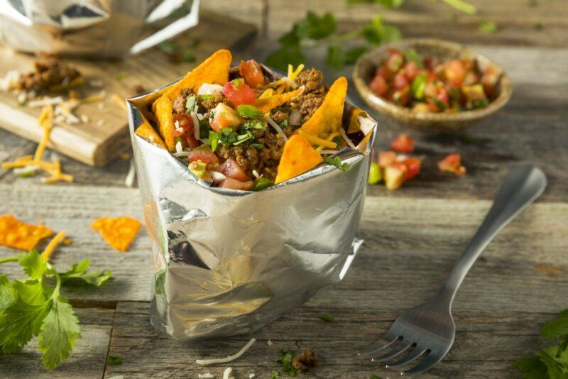 A metallic bag that contains tacos and toppings, with more ingredients in the background
