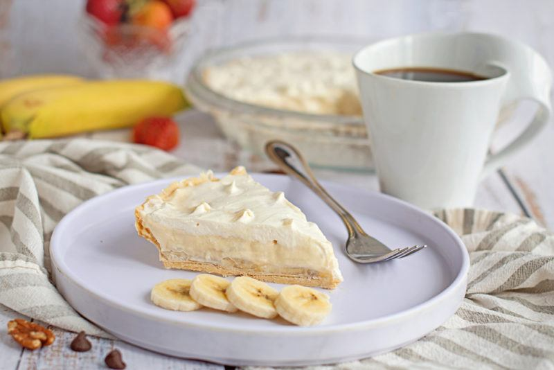 A white dish containing a banana cream pie and sliced bananas, next to a mug of coffee and ingredients for the pie