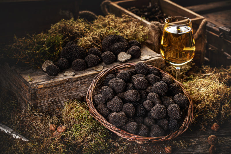 A large basket of truffles next to a glass of wine and a selection of truffles