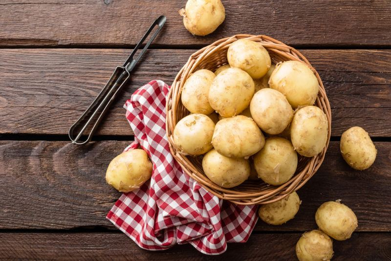 A basket on a red and wite cloth, filled with raw potatoes, next to a potato peeler