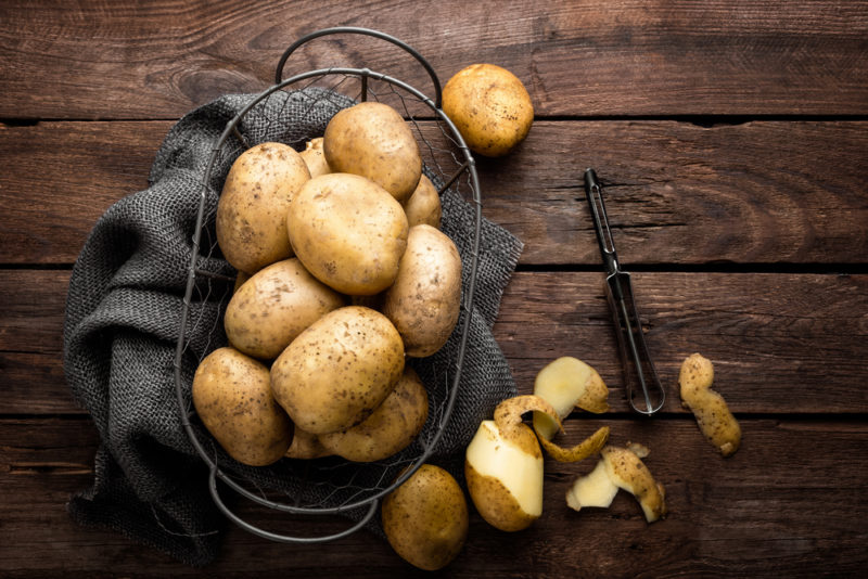 A top down image of a basket of potatoes with a black cloth, next to a partially peeled potato and a potato peeler