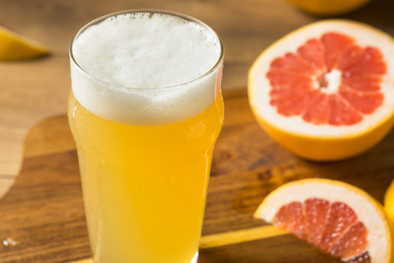 A pint glass containing shandy, next to a half grapefruit and a piece of grapefruit