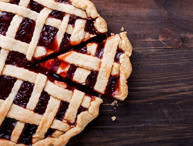 A berry pie with lattice as the top on a wooden table