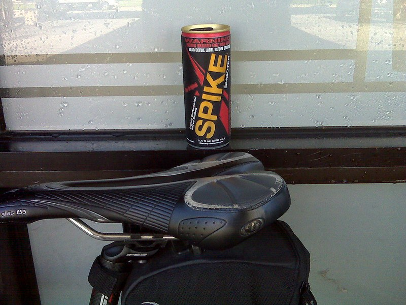 A black and gold can of Spike energy drink in front of a bike seat