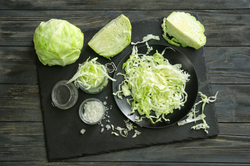 A black slate board on a wooden table with cabbage that is whole, quartered and shredded