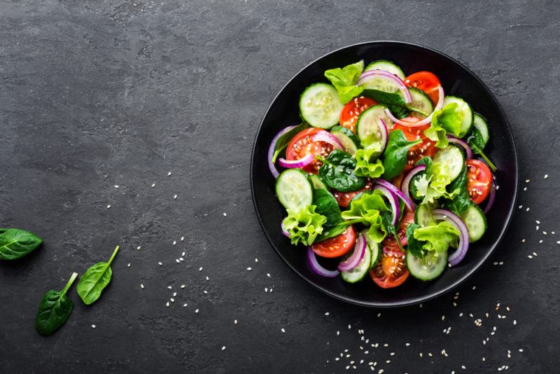 A black bowl containing a salad