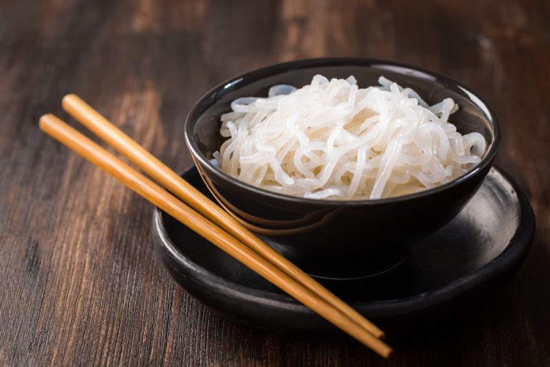 A black bowl with konjac root noodles and chopsticks