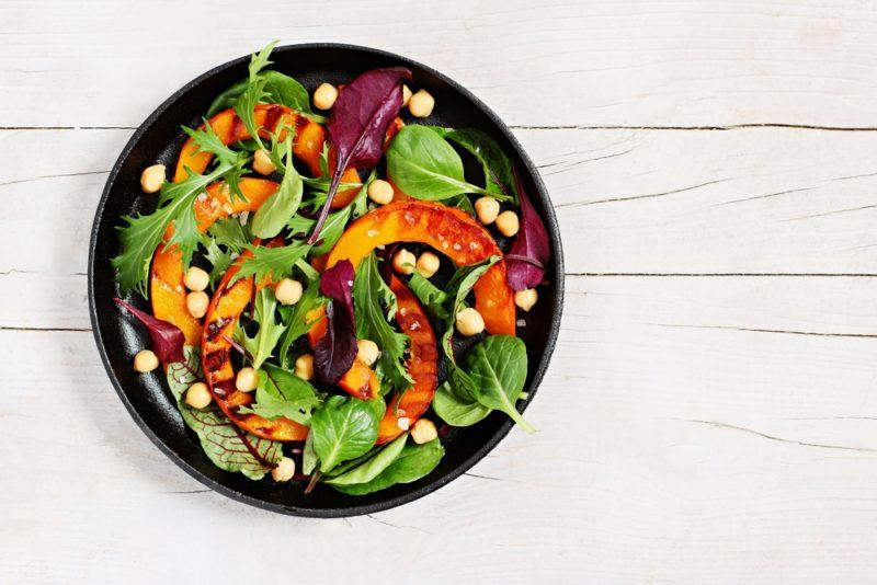 A black bowl of a vibrant salad on a white wooden table