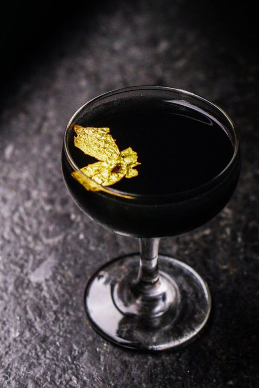 A black cocktail that uses a few gold leaves as a garnish
