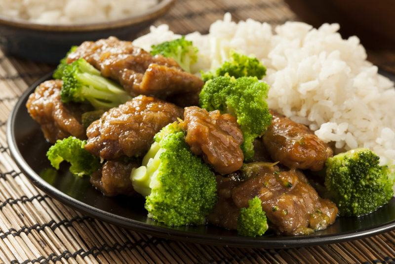 A black dish with beef, broccoli and white rice