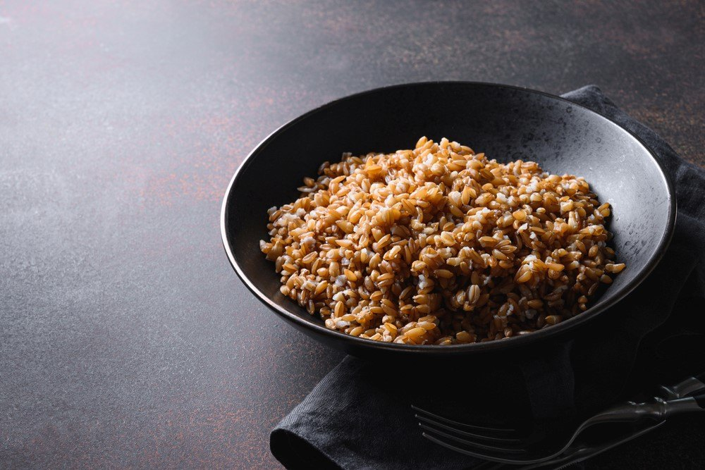A black frypan that contains cooked farro