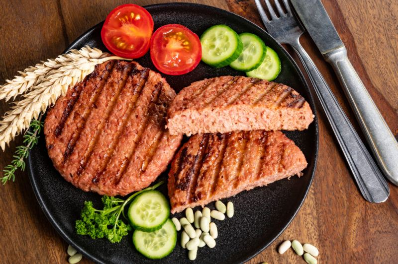 A black dish with two vegan burger patties, one of which has been cut in half. There is also some tomatoes and sliced cucumber