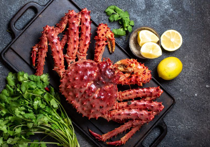 A fresh Alaskan king crab on a slate next to greens and lemon wedges