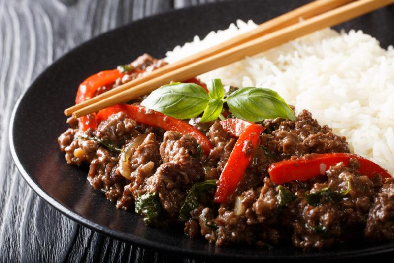 A black dish of pad gra prow and rice, with chopsticks
