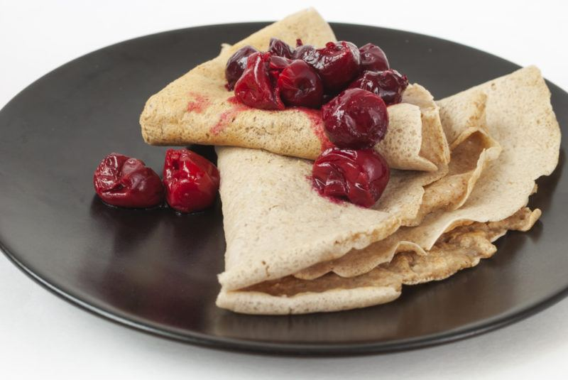 A black dish with buckwheat pancakes and berries
