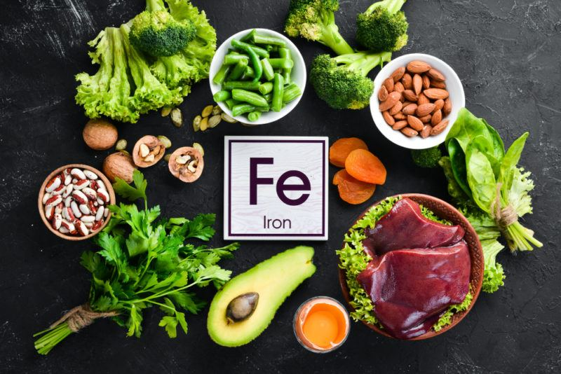 A black table with bright iron rich foods like greens and avocado, and the symbol for iron