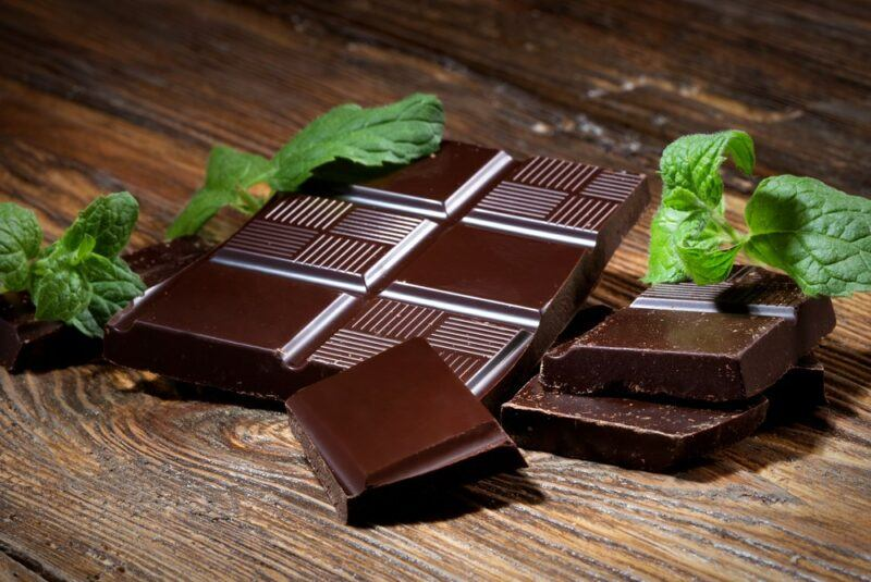 A wooden table with pieces of dark chocolate and mint leaves