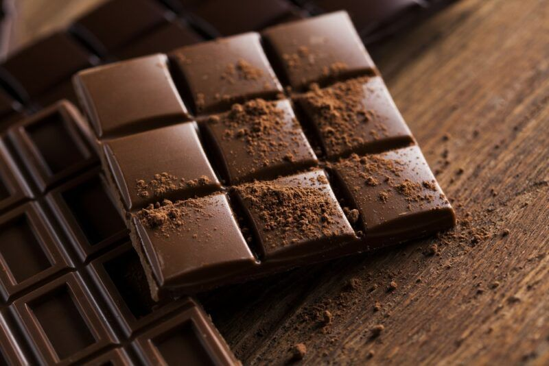 Squares of chocolate on a wooden table, including milk and dark chocolate