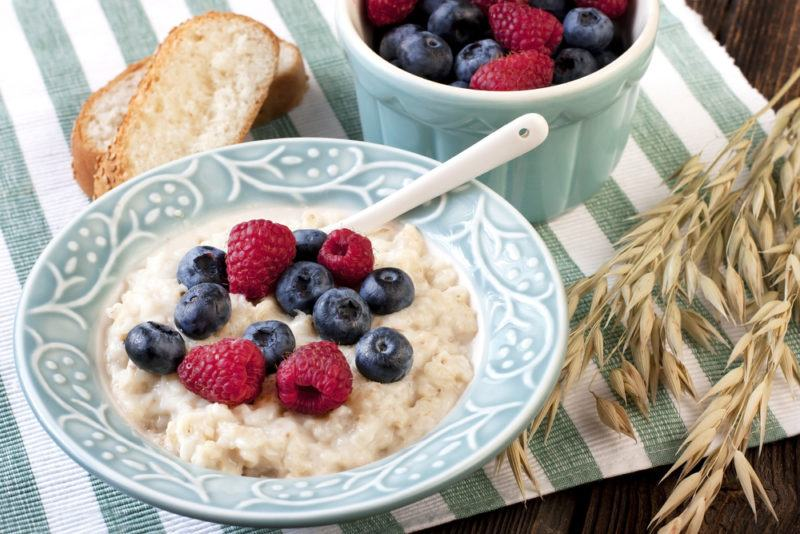 A light blue plate with instant oatmeal, raspberries and blueberries