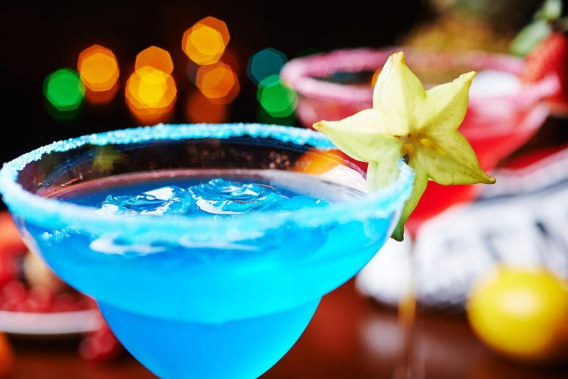 A blue margarita made using blue curacao in a cocktail glass with a strawberry daiquiri in the background