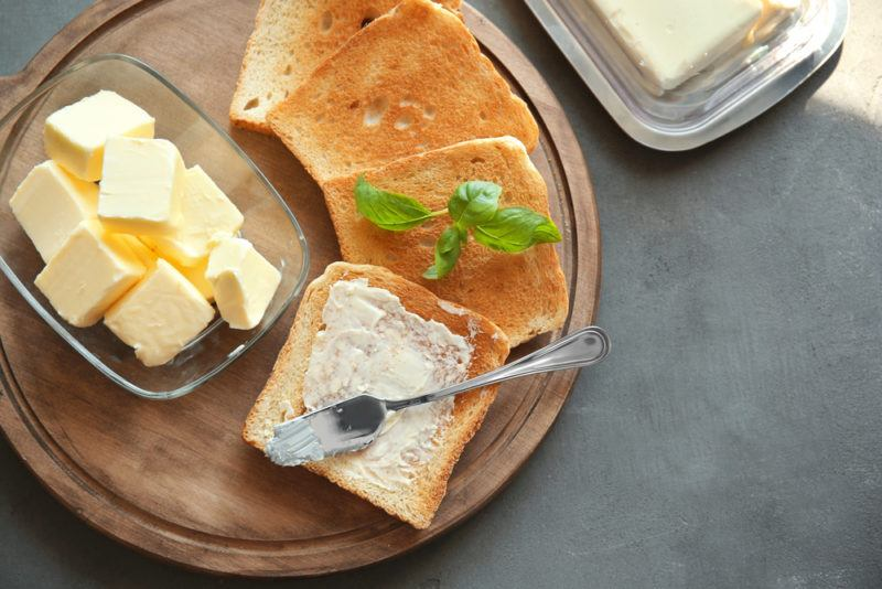 A wooden tray with slices of toast, one that's spread with butter, next to a glass container of butter cubes