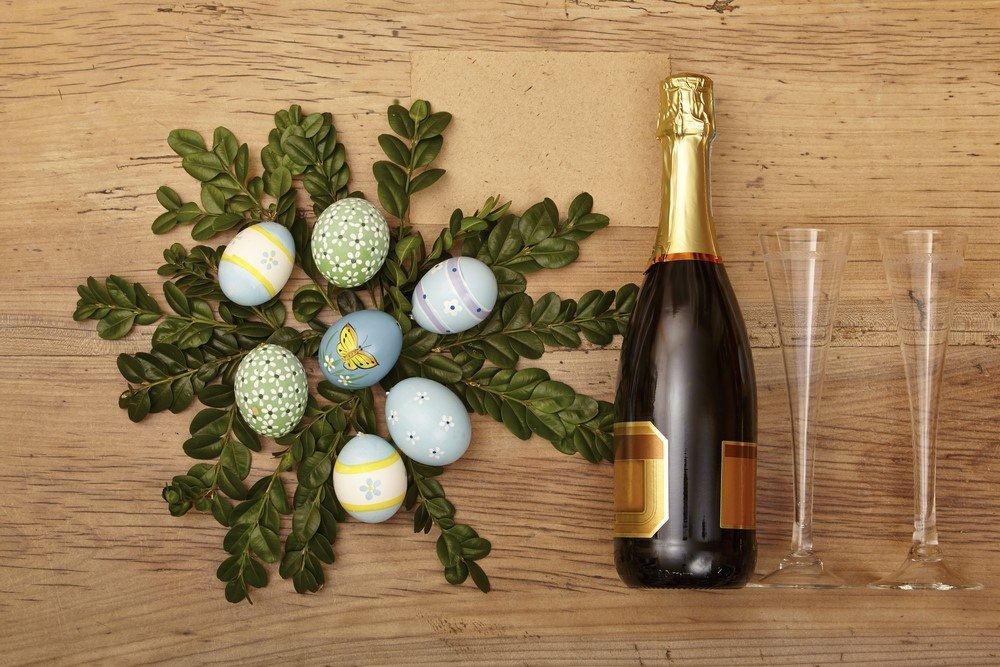 A bottle of champagne next to two glasses and an Easter decoration