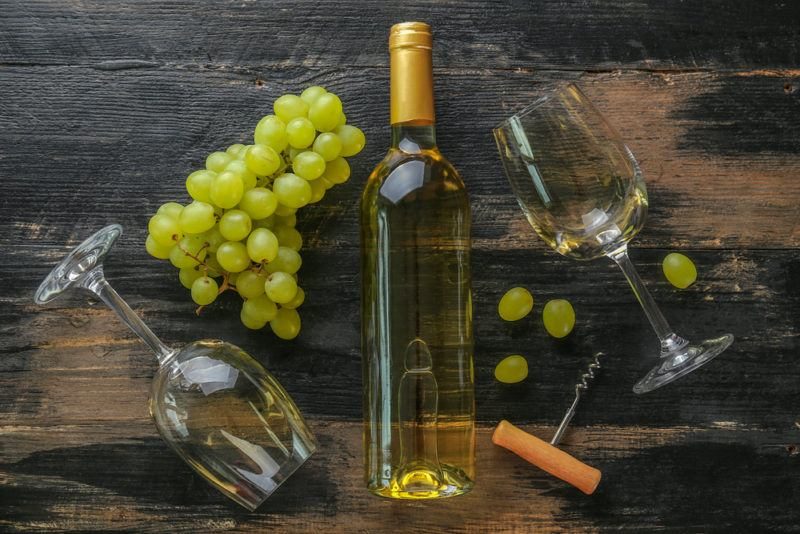 A bottle of chardonnay on a table with two glasses and a bunch of grapes