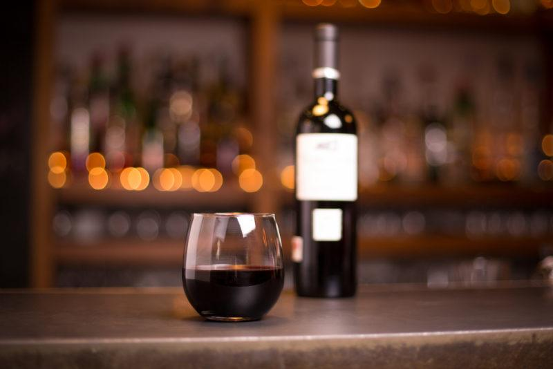 A bottle of red wine in front of a stemless glass of the wine