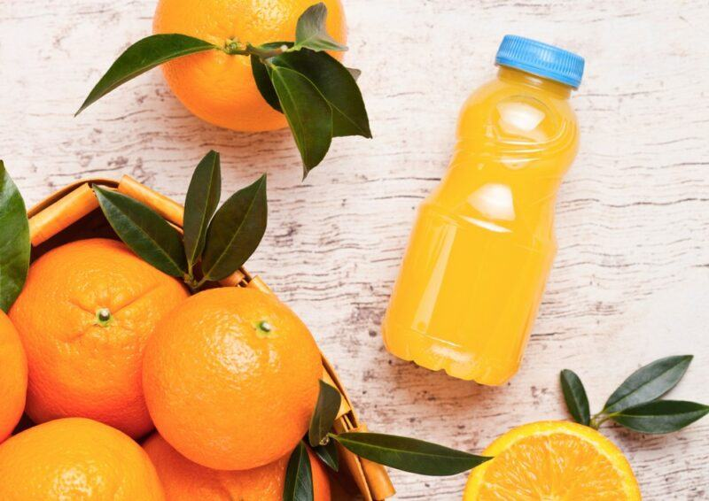 A table with a small bottle of orange juice, with a blue lid, next to a basket of fresh oranges