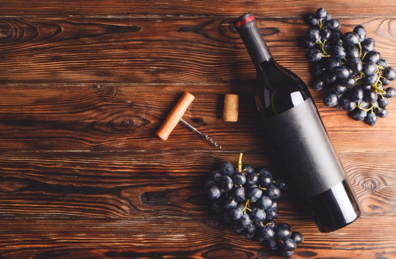 Two bunches of red grapes next to a bottle of red wine, a corkscrew and a cork