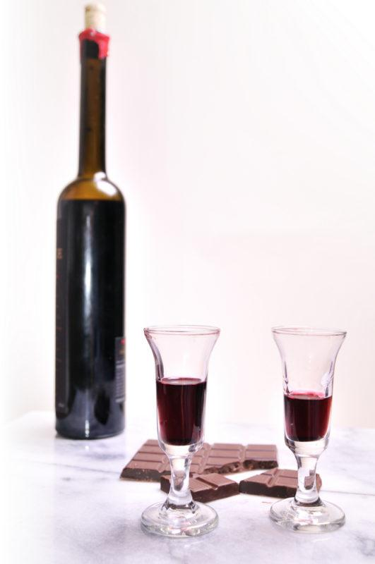 Two glasses of port next to a bottle of port and some milk chocolate