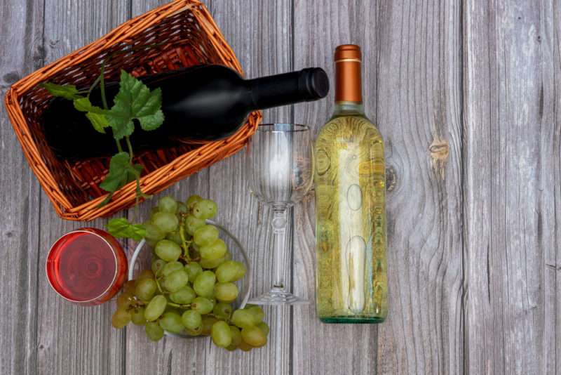 A bottle of red wine and a bottle of chenin blanc with white grapes on a wooden table