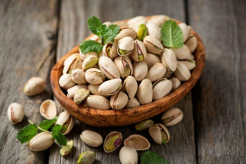 A brown bowl of pistachio nuts still in their shells on a wooden table