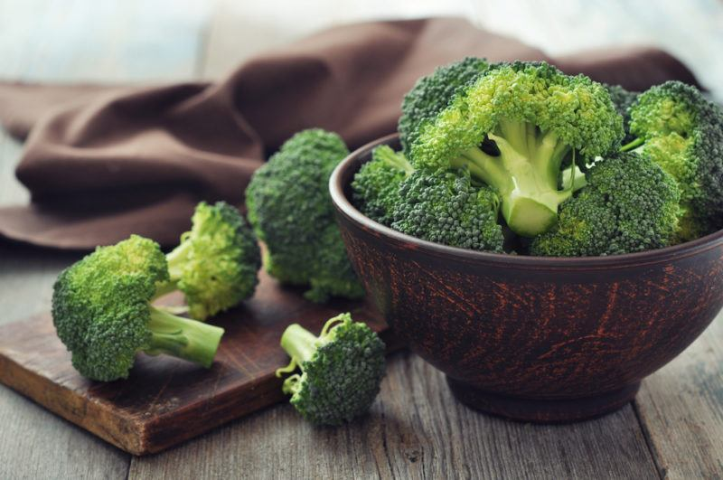 A wooden bowl with broccoli, next to a wooden board with broccoli