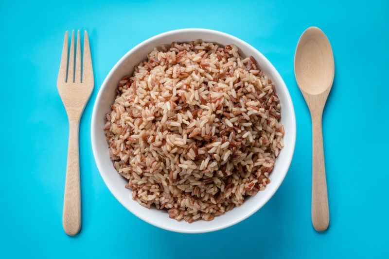 A white bowl of brown rice, with a wooden knife and fork