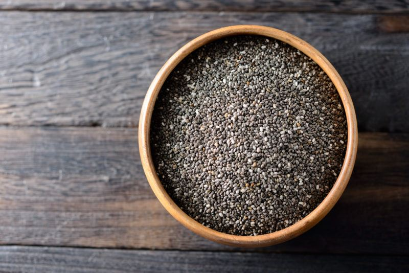 A brown bowl of chia seeds on a wooden floor