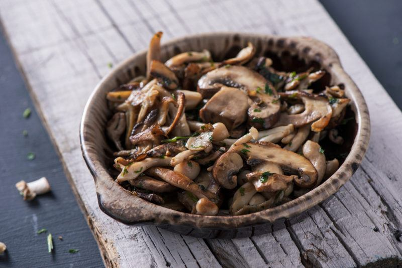 A brown bowl of cooked mushrooms